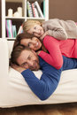 Happy family on sofa lying down Stock Photo