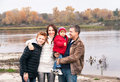 Happy family is standing near the river in the autumn day. Royalty Free Stock Photo