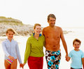 Happy family strolling on the sea shore Royalty Free Stock Photography