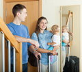 Happy family with suitcases couple toddler near door at home Royalty Free Stock Image