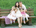 Happy family in summer city park outdoor, pregnant woman, parent and children, bright sunny day and green grass, beautiful people Royalty Free Stock Photo