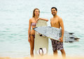 Happy family with surf boards young couple on the shore in wetsuits Royalty Free Stock Photography