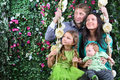 Happy family on swing look at distance near hedge of four with flowers in garden Stock Photography