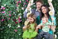 Happy family on swing look toward near hedge of four with flowers in garden Stock Photo