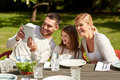 Happy family with tablet pc at table in garden Royalty Free Stock Photo