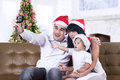 Happy family taking a photo in santa hat with camera Stock Photography