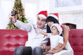 Happy family taking a photo in santa hat at home Stock Photo