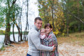 Happy family with their baby daughter spending time outdoor in the autumn park Royalty Free Stock Photo