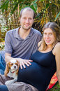 Happy family with their dog and pregnant motherin park beautiful mother outdoors at the Royalty Free Stock Photo