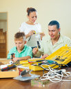 Happy family of three doing something with working tools at home Royalty Free Stock Images
