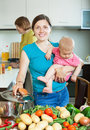 Happy family of three generations cooking with vegetables together in the kitchen Stock Images