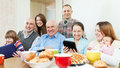 Happy family of three generations with electronic devices over tea in living room at home Stock Photo