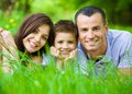 Happy family of three lying on grass Stock Image