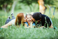 Happy family of three lying in the grass in summer park. Royalty Free Stock Photo