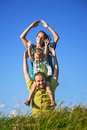 Happy family from three people have fun outdoors on grass against blue sky Stock Photography
