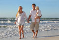 Happy Family of Three People Walking on Beach Along Ocean Royalty Free Stock Photo