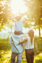 Happy family of three persons walking the grass in the park on sunset. happy daughter flying on father back Royalty Free Stock Photo