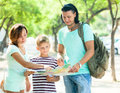 Happy family of three searching way at map paper in the city park Royalty Free Stock Photo