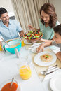 Happy family of three sitting at dining table high angle view in the home Royalty Free Stock Image