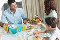 Happy family of three sitting at dining table portrait in the home Royalty Free Stock Image