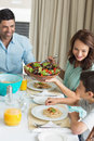 Happy family of three sitting at dining table portrait in the home Stock Image