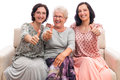 Happy family three women thumb up senior mother with adult daughters sitting on sofa showing of isolated on white background Royalty Free Stock Photo