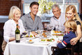 Happy family together eating in a restaurant with child and grandparents Stock Photos