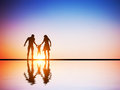 Happy family together parents and their child at sunset water reflection Stock Photography