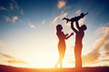 Happy family together parents with their little child at sunset father raising baby up in the air Stock Photography