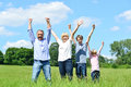 Happy family together raising their arms cheerful of four lifting up in the air Stock Photos