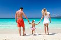 Happy family on tropic vacation mother father and daughter having fun tropical white beach Royalty Free Stock Photography