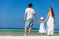 Happy family on tropical vacation back view of young beautiful beach Royalty Free Stock Photo