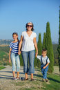 Happy family in tuscan mother with her kids having fun on vacations against cypress alley background Royalty Free Stock Photo