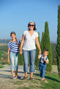 Happy family in tuscan mother with her kids having fun on vacations against cypress alley background Stock Photos