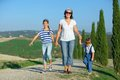 Happy family in tuscan mother with her kids having fun on vacations against cypress alley background Stock Photography