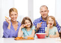 Happy family with two kids eating at home food children hapiness and people concept Stock Photos