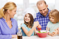 Happy family with two kids eating at home food children hapiness and people concept making dinner Stock Photography
