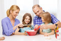 Happy family with two kids eating at home food children hapiness and people concept making dinner Stock Photos