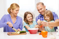 Happy family with two kids making dinner at home food children hapiness and people concept Royalty Free Stock Photo