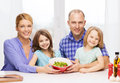 Happy family with two kids with salad at home food children hapiness and people concept Royalty Free Stock Photo