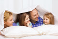 Happy family with two kids under blanket at home children and concept Stock Photography