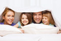 Happy family with two kids under blanket at home children and concept Stock Images