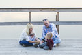 Happy family of two parents and  children, one boys,  baby girl, sitting together on the river jetty. Royalty Free Stock Photo