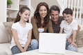 Happy Family Using Laptop Computer on Sofa at Home Royalty Free Stock Photography