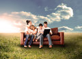 Happy family using the laptop in a field couch sunny countryside Royalty Free Stock Image