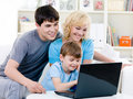 Happy family using laptop at home Stock Photos
