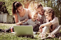 Happy family using laptop, sitting on the green grass. Royalty Free Stock Photo