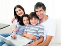 Happy family using a laptop sitting on sofa Royalty Free Stock Photo