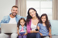 Happy family using modern technologies while sitting on sofa portrait of at home Stock Photo