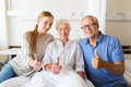 Happy family visiting senior woman at hospital medicine support gesture health care and people concept men and young women her Royalty Free Stock Images